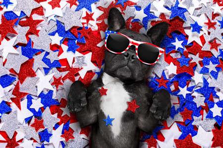 julio: Bulldog francés agitando una bandera de los EE.UU. y la victoria o la paz dedos en la independencia día 4 de julio con gafas de sol