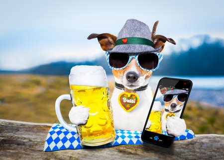 bavarian jack russell dog holding  a beer mug  outdoors by the river and mountains  , ready for the beer party celebration festival in munich, taking a selfie