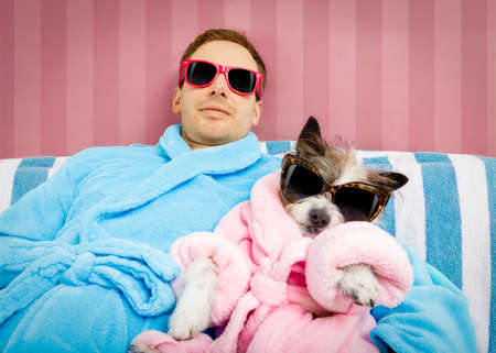 cool funny couple of   poodle dog  and owner  both resting and relaxing in   spa wellness salon center ,wearing a  bathrobe and fancy sunglasses, Banque d'images
