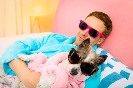 cool funny couple of   poodle dog  and owner  both resting and relaxing in   spa wellness salon center ,wearing a  bathrobe and fancy sunglasses, Archivio Fotografico