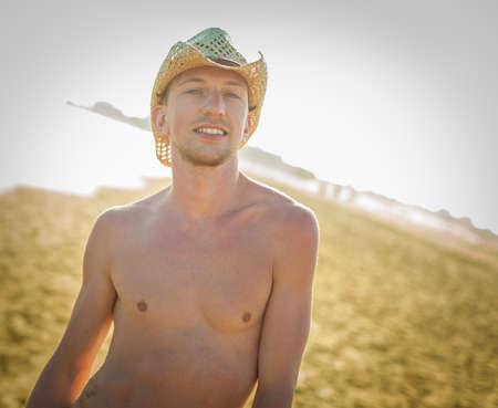 sexy gay man at the beach of gran canaria , maspalomas dunes , ocean behind