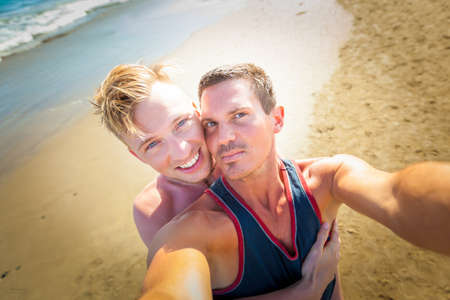 gay couple in love at the beach embracing together,  just married close to the ocean shore at the sea Stock Photo