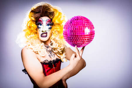cool drag queen with spectacular makeup, glamorous stylish look, posing with   proud and  style for lgtb equality gay rights with disco ball 스톡 콘텐츠