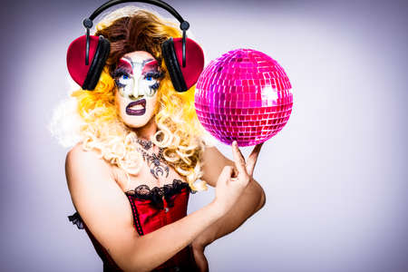 cool drag queen with spectacular makeup, glamorous stylish look, posing with   proud and  style for lgtb equality gay rights with disco ball Archivio Fotografico