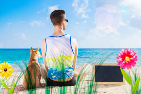 dog and owner sitting close together at the beach on summer vacation holidays, watching sunset or sunrise , empty blank blackboard or banner to the side