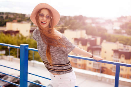 Fashion lifestyle portrait of young happy pretty woman laughing and having fun on the roof at nice sunny summer day, stylish vintage outfit,bright fresh colors.