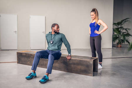The black coach show to the young girl how to perform the exercise in the gym - Afro american personal trainer is showing the exercise at beautiful girl in the gym