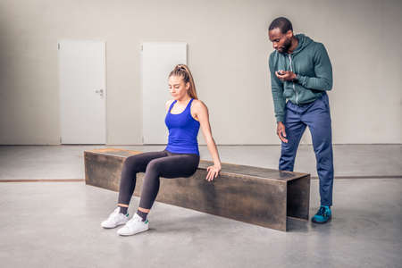 Athletic girls doing fitness exercise with black personal trainer in fitness gym, exercise fitness, workout and sport training concept Stock Photo