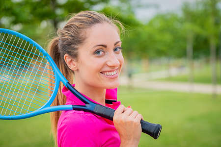Portrait of tennis player girl holding racket outside - Portrait beautiful blonde girl who is playing tennis in stylish sportswear holding racket in hand, preparing to play tennis outdoors - Active Lifestyle Zdjęcie Seryjne