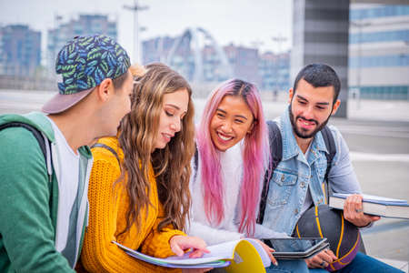 Multiethnic students joking and talking sitting on the bench together outdoors in a university - Group of happy young teenagers studying with books and tablets