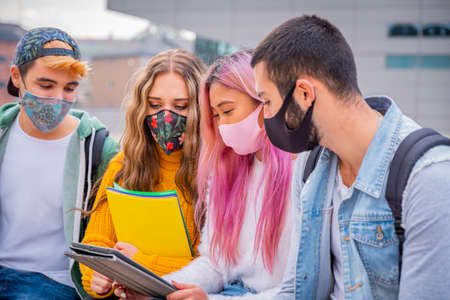 Multiethnic students sitting with mask on the bench together in a university - Group of young teenagers studying on the bench with protective mask in pandemic covid 19 period 免版税图像