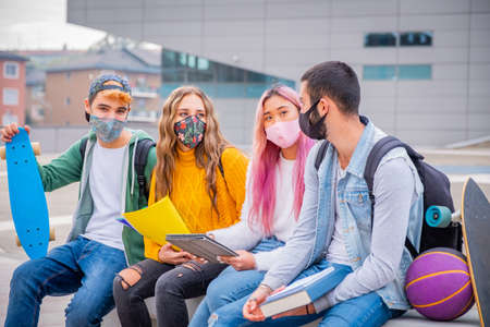 Multiethnic students sitting with mask on the bench together in a university - Group of young teenagers studying on the bench with protective mask in pandemic covid 19 period 免版税图像 - 157949252