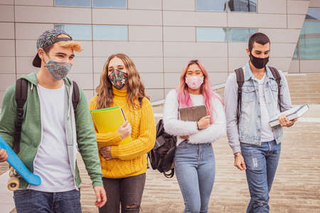 Multiethnic students walking with mask together out the university - Group of young teenagers arguing and walking around the street with protective mask in pandemic covid 19 period