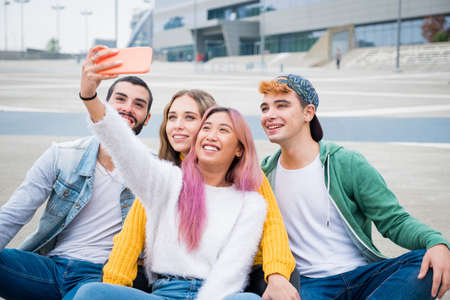 Group of teneegers laughing and jocking together while doing a videocall with theyrs friends - Group of friends in holiday taking a selfie for remember this special moment
