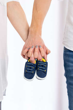 Close up picture of happy couple of pregnant mother with father holding hands small shoes. Couple hands holding baby boys shoes