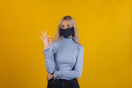 Its good, I like it. Closed-up portrait of young blonde girl in a black mask shows gesture ok on yellow background and looking at camera. Coronavirus pandemic time