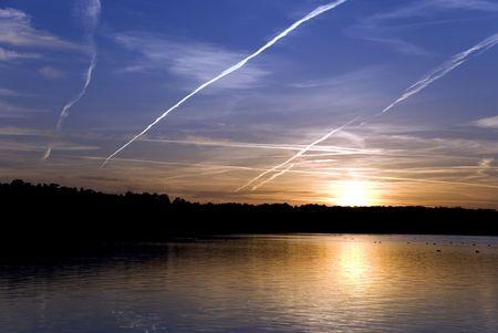 cloud drift: The sun shining on horizon behind clouds Stock Photo
