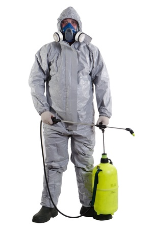 A pest control worker wearing a mask, hood, protective suit and dual air filters holding a hose to help exterminate rats and other vermin  photo