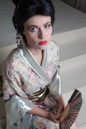 Traditional Japanese geisha woman with extreme makeup and traditional clothing photo
