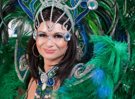 Portrait of young woman in green carnival costume, close up