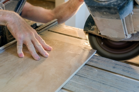 A wet saw cutter is being used to cut floor tile Stock Photo - 20443293