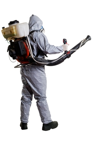 A pest control worker wearing a mask, hood, protective suit and dual air filters holding a hose to help exterminate rats and other vermin  Standard-Bild