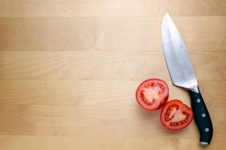 Wooden cutting board with kitchen knife and tomatoes photo