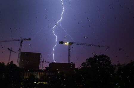 Lightning strike in a construction area viewed through glass with rain drops. photo