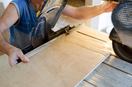 A wet saw cutter is being used to cut floor tile Stock Photo