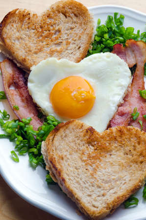bacon love: Fried egg in the shape of a heart with bacon and toast. Stock Photo