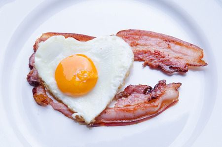 bacon love: Fried egg in the shape of a heart with bacon.
