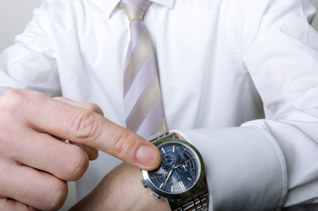 A man in a white shirt and a tie pointing at his watch photo