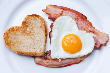 Heart-shaped toast next to a heart-shaped fried egg on a piece of bacon on a plate Stock Photo