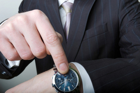 A man in a suit, a white shirt and a tie pointing at his watch