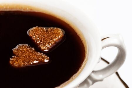 Two cubes of heart-shaped sugar floating in a cup of coffee