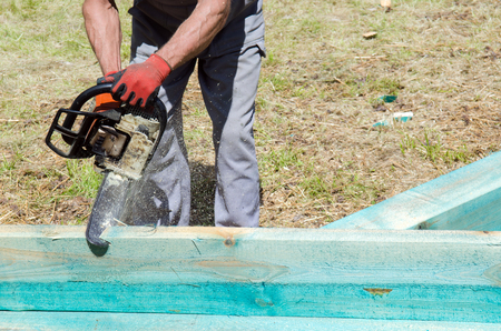 Man sawing a wooden beam with a chain saw Stock Photo