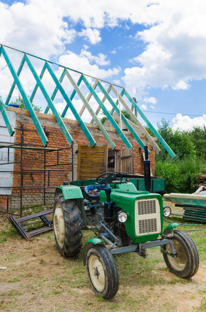 A construction of a roof with a tractor in front of the renovated building