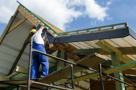 A worker standing on the scaffolding and finishing a roof
