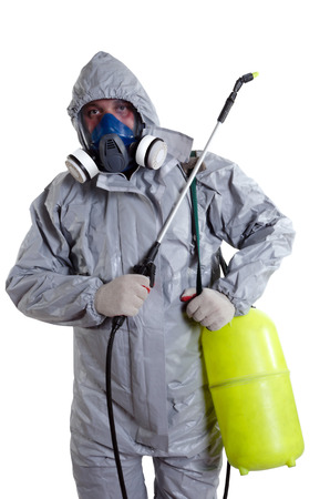 A pest control worker wearing a mask, hood, protective suit and dual air filters holding a hose to help exterminate rats and other vermin. photo