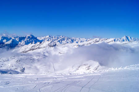 snow in the mountains, fog in the distance, blue sky, ski run, view of snow-capped mountains Banque d'images
