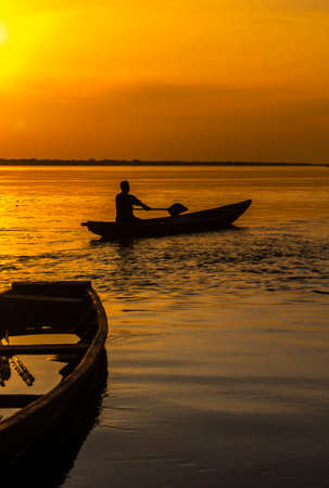 A traditional Peruvian boat, a canoe called Peke Peke, used in the Amazonian jungle. View during sunset, Amazon river. The man is sailing a typical boat on the Amazon River