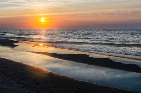sunset over the Baltic Sea. Sandy beach. The sun's rays are reflected in the water.