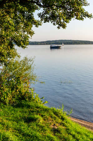 Masurian lake, motor boat and yachts in the distance. Sunny day. People rest on the yacht. September 14, 2020 Mazry, ÅšwiÄ™cajty lake, Poland
