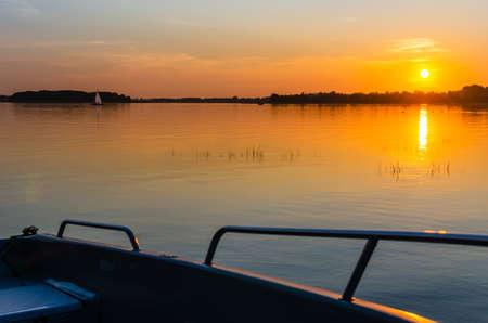 Masurian lake, sunset, motor boat on the lake shore.