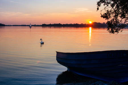 Masurian lake, sunset, motor boat on the lake shore. In the distance a swan and a sailboat