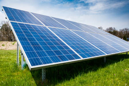 Solar panels standing on the ground, green grass, forest in the distance