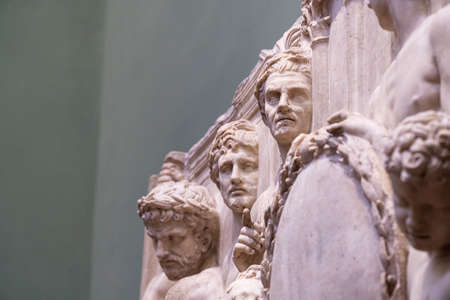 Photo of three heads coming out of a marble sculpture