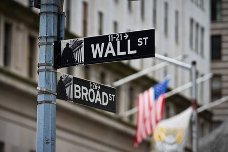 Wall Street sign with American flag in the Financial District of Lower Manhattan Stock Photo