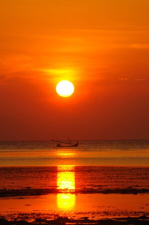 Silhouette of a small fishing boat gliding across the calm waters of the Bama Beach in East Java at dawn with the golden sunrise