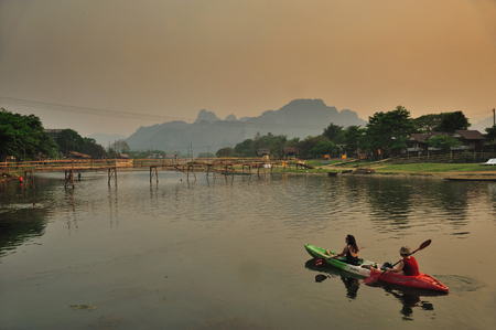 A couple tourists are rowing kayak boat during sunset on the river of Nam Song in Vang Vieng, Laos Stock Photo